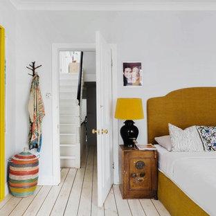 Diseño de dormitorio bohemio, de tamaño medio, con suelo de madera clara y paredes grises