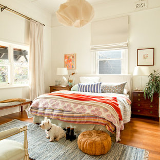Eclectic medium tone wood floor and orange floor bedroom photo in Perth with white walls