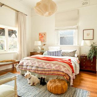 Ispirazione per una camera da letto bohémian con pareti bianche, pavimento in legno massello medio e pavimento arancione