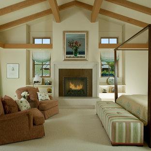 Imagen de dormitorio bohemio con paredes beige, moqueta, chimenea tradicional y marco de chimenea de metal