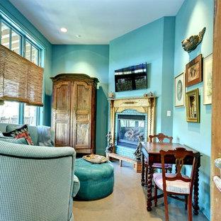 Diseño de dormitorio principal, bohemio, de tamaño medio, con paredes azules, suelo de cemento, chimenea de esquina, marco de chimenea de ladrillo y suelo gris