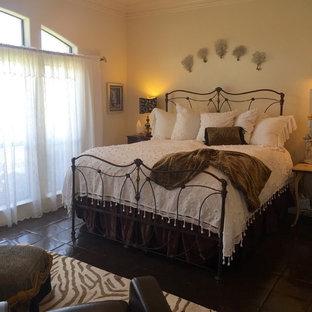 Imagen de dormitorio principal, ecléctico, grande, con paredes amarillas, suelo de baldosas de terracota, chimenea tradicional y marco de chimenea de madera
