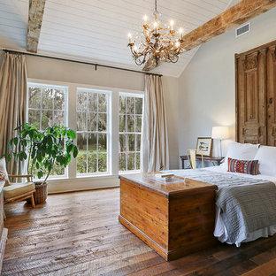 Diseño de dormitorio principal, de estilo americano, con paredes grises y suelo de madera en tonos medios