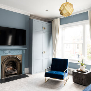 Contemporary master bedroom in London with blue walls, carpet, a standard fireplace, a metal fireplace surround and grey floor.