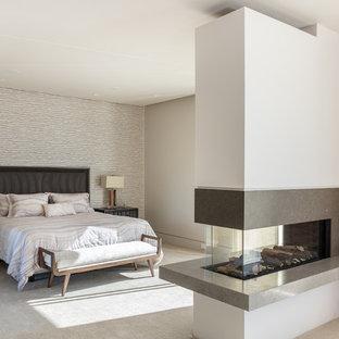Idee per una grande camera matrimoniale moderna con pareti bianche, moquette, camino bifacciale, cornice del camino in pietra e pavimento beige