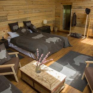 Esempio di una camera matrimoniale rustica di medie dimensioni con pavimento in legno massello medio e stufa a legna