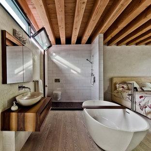 Immagine di una camera matrimoniale moderna con pareti beige e parquet chiaro