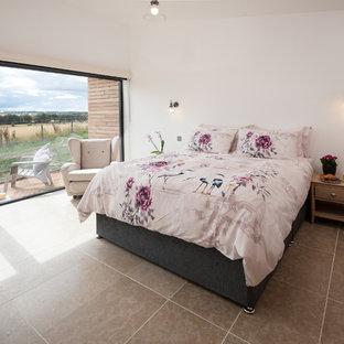 На фото: хозяйская спальня среднего размера в современном стиле с белыми стенами, полом из терракотовой плитки и серым полом