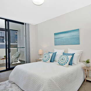 Design ideas for a beach style master bedroom in Sydney with grey walls, carpet and brown floor.
