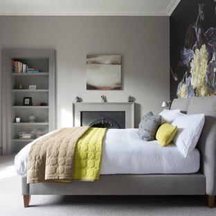 Foto på ett vintage sovrum, med grå väggar, heltäckningsmatta, en hängande öppen spis, en spiselkrans i metall och grått golv