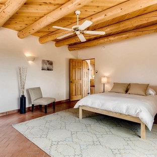 Modelo de dormitorio principal, de estilo americano, de tamaño medio, sin chimenea, con paredes blancas, suelo de ladrillo y suelo marrón