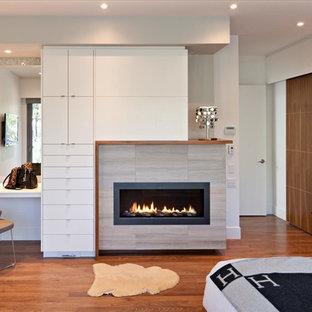 Cette photo montre une chambre parentale tendance de taille moyenne avec un mur blanc, un sol en bois foncé, une cheminée ribbon, un manteau de cheminée en carrelage et un sol beige.