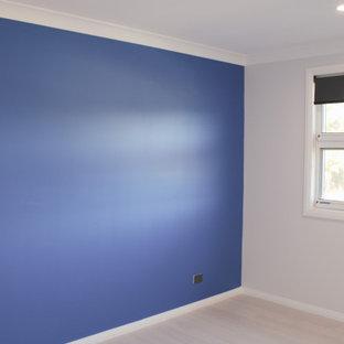 Modelo de habitación de invitados minimalista, de tamaño medio, con paredes azules y suelo de madera clara