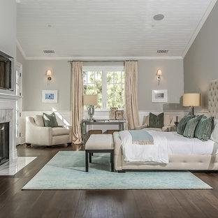Foto de dormitorio principal, moderno, grande, con paredes grises, suelo de madera oscura, chimenea tradicional, marco de chimenea de madera y suelo marrón