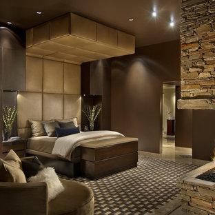 Ejemplo de dormitorio principal, actual, grande, con paredes marrones, chimenea de esquina, marco de chimenea de piedra y moqueta