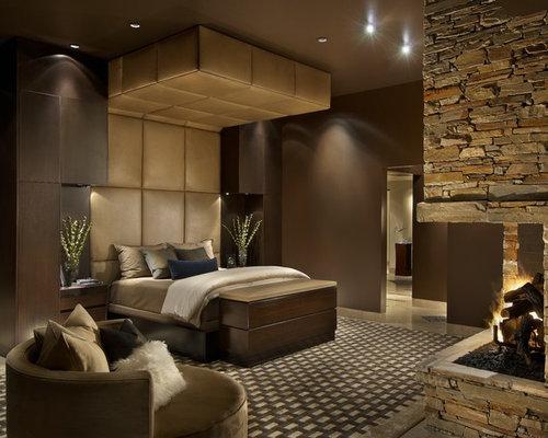 Camera da letto con camino ad angolo e pareti marroni - Foto e ...