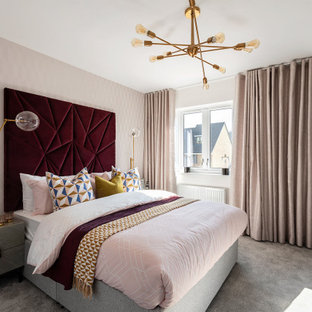 Photo of a contemporary bedroom with pink walls, carpet and grey floors.