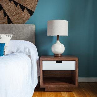 Exemple d'une chambre parentale éclectique de taille moyenne avec un mur bleu, un sol en bois clair et aucune cheminée.