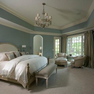Diseño de dormitorio principal, tradicional, extra grande, con paredes azules, moqueta, chimenea tradicional y marco de chimenea de piedra