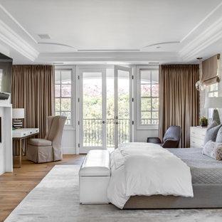 Idée de décoration pour une grand chambre parentale méditerranéenne avec un mur blanc, un sol en bois brun, une cheminée standard, un manteau de cheminée en carrelage et un sol beige.