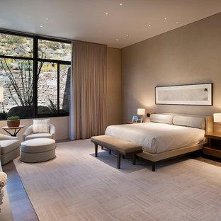 Imagen de dormitorio principal, minimalista, extra grande, con paredes beige, suelo de madera en tonos medios, chimenea tradicional y marco de chimenea de yeso