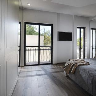 Ispirazione per una grande camera degli ospiti design con pareti bianche, pavimento in compensato e nessun camino