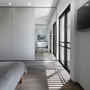 Imagen de habitación de invitados contemporánea, grande, sin chimenea, con paredes blancas y suelo de contrachapado