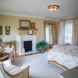 Idee per una grande camera matrimoniale vittoriana con pareti beige, camino classico, cornice del camino in pietra, pavimento marrone e pavimento in legno massello medio