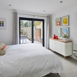 Imagen de dormitorio principal, moderno, pequeño, con paredes blancas, suelo de pizarra y suelo gris