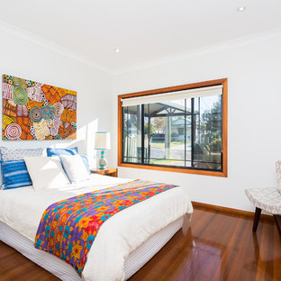 Small eclectic guest bedroom in Sydney with white walls, dark hardwood floors and brown floor.