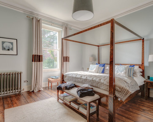 large master medium tone wood floor bedroom photo in devon with blue walls