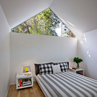 This is an example of a small contemporary bedroom in San Francisco with white walls and medium hardwood flooring.