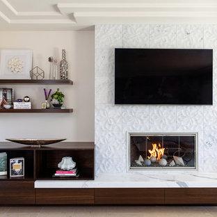 Imagen de dormitorio principal, moderno, de tamaño medio, con paredes blancas, suelo de piedra caliza, chimenea tradicional, marco de chimenea de piedra y suelo gris