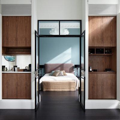 Large trendy master dark wood floor bedroom photo in London with blue walls