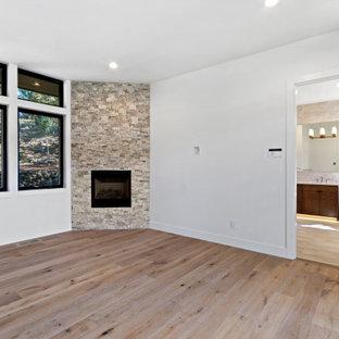 Стильный дизайн: большая хозяйская спальня в современном стиле с белыми стенами, светлым паркетным полом, угловым камином и фасадом камина из каменной кладки - последний тренд