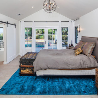 This is an example of a large transitional master bedroom in San Diego with grey walls, porcelain floors and brown floor.