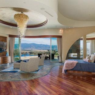 Ejemplo de dormitorio principal, contemporáneo, extra grande, con paredes beige, chimenea de doble cara, marco de chimenea de piedra, suelo marrón y suelo de madera en tonos medios