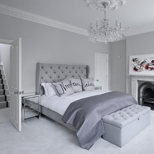 This is an example of a contemporary master bedroom in London with grey walls, carpet, a standard fireplace and grey floors.