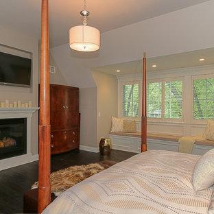 Идея дизайна: большая хозяйская спальня в стиле кантри с бежевыми стенами, темным паркетным полом, стандартным камином и фасадом камина из штукатурки