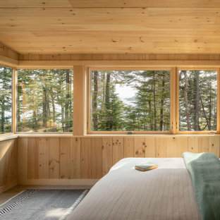 Photo of a mid-sized country master bedroom in Portland Maine with brown walls, medium hardwood floors and grey floor.