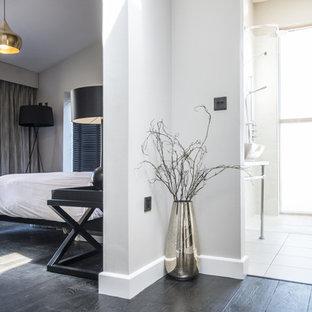 Modelo de dormitorio principal, contemporáneo, grande, con suelo de bambú, paredes beige y suelo negro