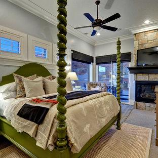Cette image montre une chambre traditionnelle avec un mur gris, une cheminée d'angle et un manteau de cheminée en pierre.