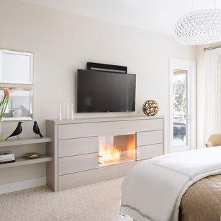 На фото: большая хозяйская спальня в стиле современная классика с серыми стенами, ковровым покрытием, стандартным камином и фасадом камина из дерева