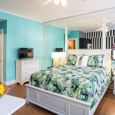 Island style medium tone wood floor and brown floor bedroom photo in Miami with blue walls