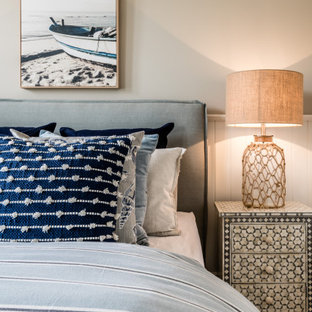 Mid-sized beach style guest bedroom in Geelong with grey walls and brown floor.