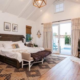 Idee per una camera matrimoniale country con pareti bianche, pavimento in legno massello medio, stufa a legna, cornice del camino in metallo e pavimento beige