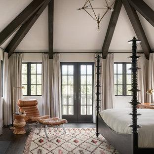 Modelo de dormitorio principal, mediterráneo, con paredes blancas, suelo de madera oscura, chimenea tradicional y suelo marrón