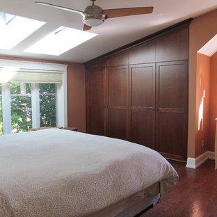 Imagen de dormitorio tipo loft, de estilo americano, pequeño, sin chimenea, con parades naranjas, suelo de madera en tonos medios y suelo marrón
