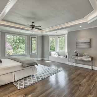 Transitional dark wood floor and brown floor bedroom photo in Portland with gray walls, a corner fireplace and a tile fireplace