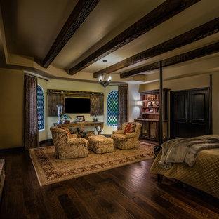 Foto de dormitorio principal, mediterráneo, con suelo de madera en tonos medios, chimenea tradicional y marco de chimenea de ladrillo